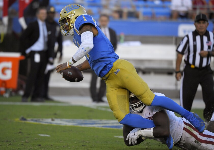 UCLA quarterback Dorian Thompson-Robinson, left, is sacked by Oklahoma linebacker Jalen Redmond during the first half.