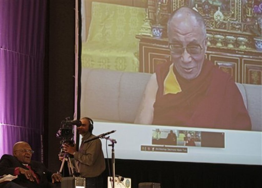 South African Archbishop Desmond Tutu, sitting at left, speaks during a live video link with Tibetan spiritual leader the Dalai Lama, right on screen, near the city of Cape Town, South Africa, Saturday, Oct. 8, 2011. The Dalai Lama has sharply criticized China, which is accused of blocking him from traveling to South Africa to celebrate Archbishop Desmond Tutu's 80th birthday. Instead of speaking in person at a southern South African university Saturday, the Tibetan spiritual leader answered questions via a video link.(AP Photo/Schalk van Zuydam)