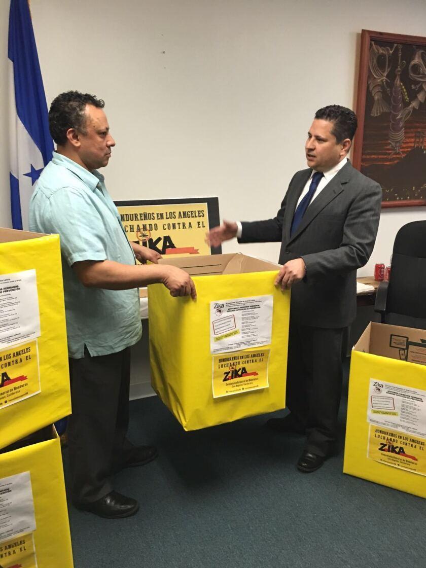 El cónsul Pablo Ordóñez entrega una de las cajas para captar donativos de repelentes y mosquiteros en Los Ángeles.