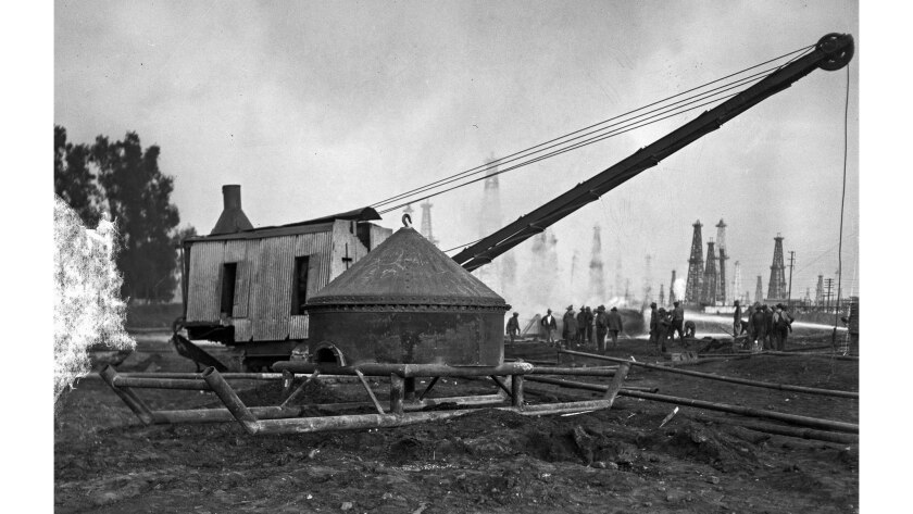 Nov. 4, 1928: The five-ton steel cap sits in front of the steam-powered crane that placed it on burn