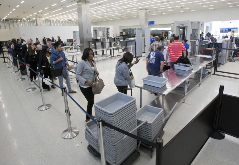 Viajeros se alinean en un puesto de control de seguridad en el Aeropuerto Internacional de Los Ángeles. La Administración de Seguridad del Transporte (TSA) probó brevemente un nuevo procedimiento que obligaba a los pasajeros a retirar el material de lectura de sus equipajes.