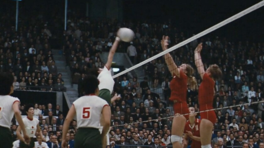 """A woman volleyball player soars above the net to spike a ball in the documentary """"The Witches of the Orient."""""""