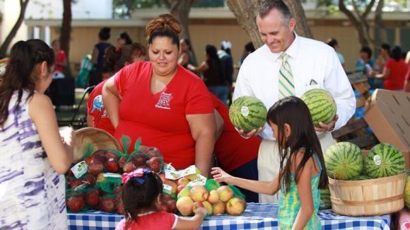El director asistente Gannon Burks (derecha) ayuda a distribuir alimentos durante el mercado de agricultores mensual en Santa Ana High School.
