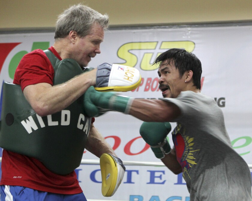 Manny Pacquiao, right, connects to the chest of trainer Freddie Roach during a workout in northern Philippines in March.