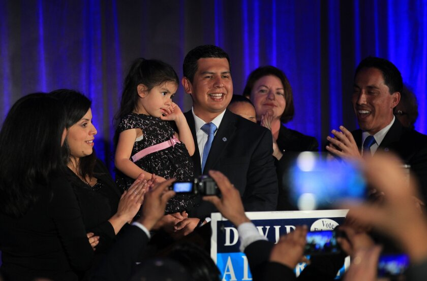 Mayoral candidate David Alvarez addresses Supporters during his election night party at the San Diego Public Market, alongside his wife Xochitl Alvarez and daughter Izel Alvarez. Assembly member Toni Atkins (2nd R) and Interim Mayor Todd Gloria (R) join them onstage.