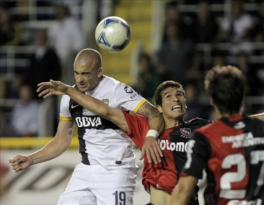 Santiago Silva (i) de Boca Juniors y Marcos Cáceres (d) de Newells Old Boys luchan por el balón durante el partido por la fecha 15 del Torneo Inicial del fútbol argentino, disputado el pasado 15 de noviembre. EFE/Archivo