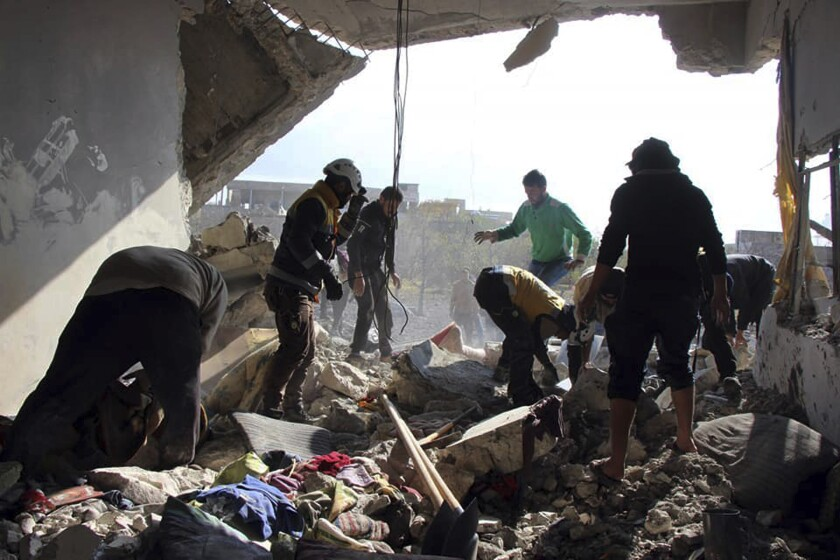 This photo released by the opposition Syrian Civil Defense rescue group, also known as White Helmets, which has been authenticated based on its contents and other AP reporting, shows Civil Defense workers and people searching for victims under the rubble of a destroyed building that was hit by airstrikes in the village of Ibdeita, in Idlib province, Syria, Saturday, Dec. 7, 2019. Airstrikes on areas in the last major rebel stronghold in northwest Syria on Saturday killed at least 18 people, including women and children, and wounded others as a three-month truce crumbles, opposition activists said. (Syrian Civil Defense White Helmets via AP)