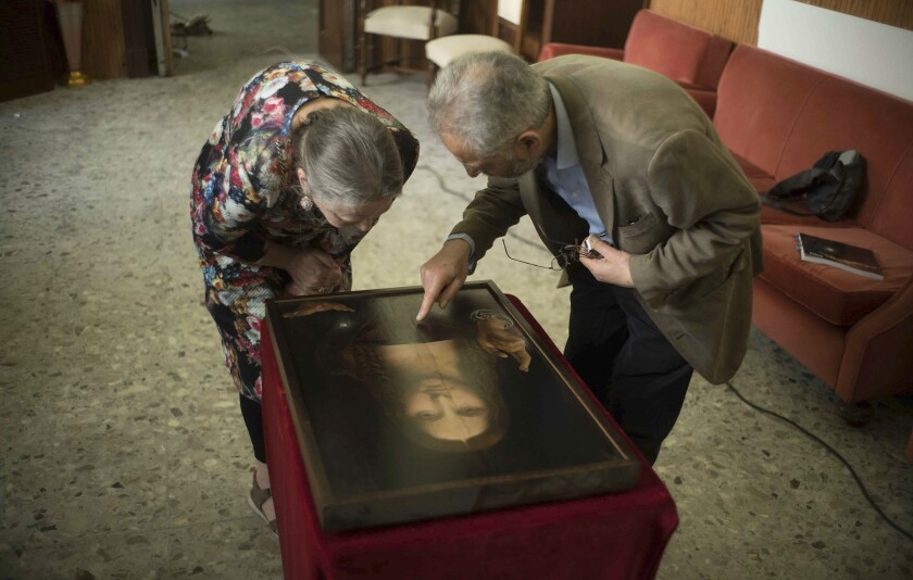 Dianne Modestini, left, and Ashok Roy inspect the Naples copy of the Salvator Mundi in a scene from 'The Lost Leonardo'