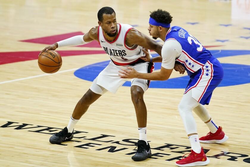 Portland Trail Blazers' Rodney Hood, left, tries to dribble past Philadelphia 76ers' Seth Curry during the first half of an NBA basketball game, Thursday, Feb. 4, 2021, in Philadelphia. (AP Photo/Matt Slocum)