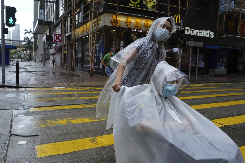People make their way on an empty street as Typhoon Kompasu passes in Hong Kong Wednesday, Oct. 13, 2021. Hong Kong suspended classes, stock market trading and government services as the typhoon passed south of the city Wednesday. (AP Photo/Vincent Yu)