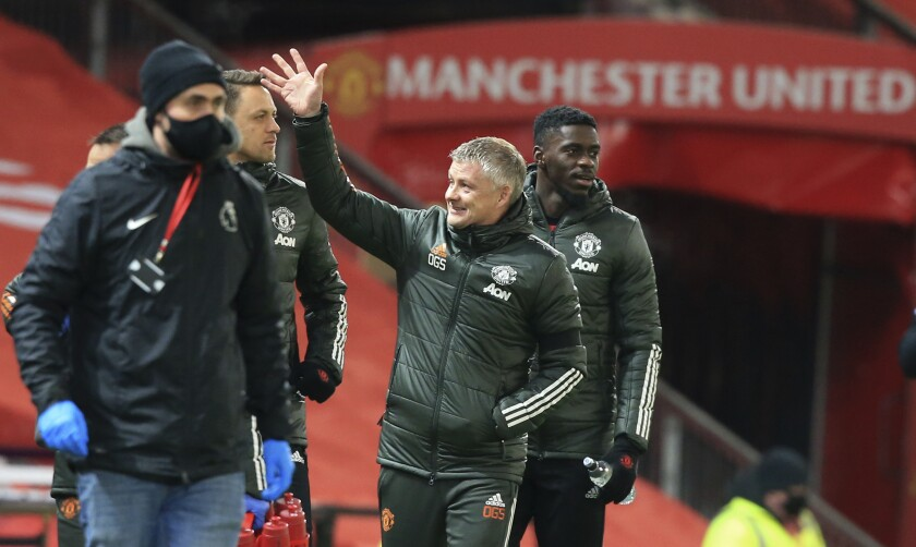 Manchester United's manager Ole Gunnar Solskjaer waves towards the directors box as he walks to the technical area ahead of the English Premier League soccer match between Manchester United and Aston Villa at Old Trafford in Manchester, England, Friday, Jan. 1, 2021. (Lindsey Parnaby/ Pool via AP)