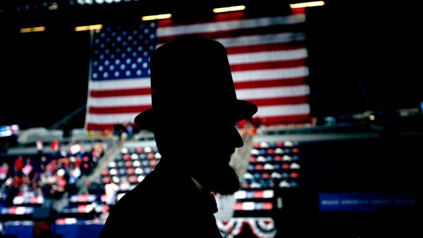 A man dressed as Abraham Lincoln walks through the crowd before the arrival of President Donald Trum