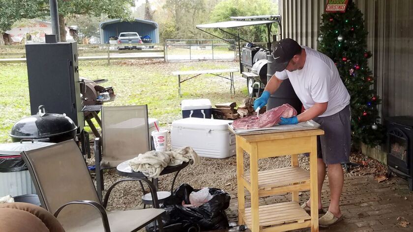C. J. Veazey trims brisket to sell during the holiday. Veazey's wife, City Secretary Tanya Veazey,
