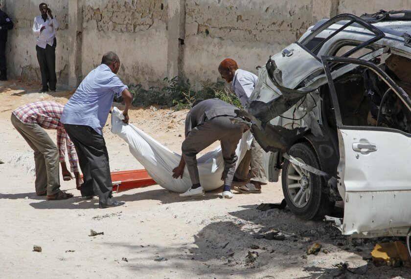 Somali officials remove the body of former Somali defense minister Muhyadin Mohamed Haji, from the scene of a car bomb in Mogadishu, Somalia, Monday, Feb. 15, 2016.  Muhyadin Mohamed Haji worked under Somali's interim government in 2008. (AP Photo/Farah Abdi Warsameh)