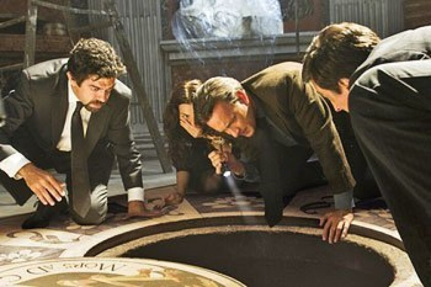 Tom Hanks, with Pierfrancesco Favino (left), Ayelet Zurer and David Pasquesi, sheds light on buried secrets. (Columbia Pictures)