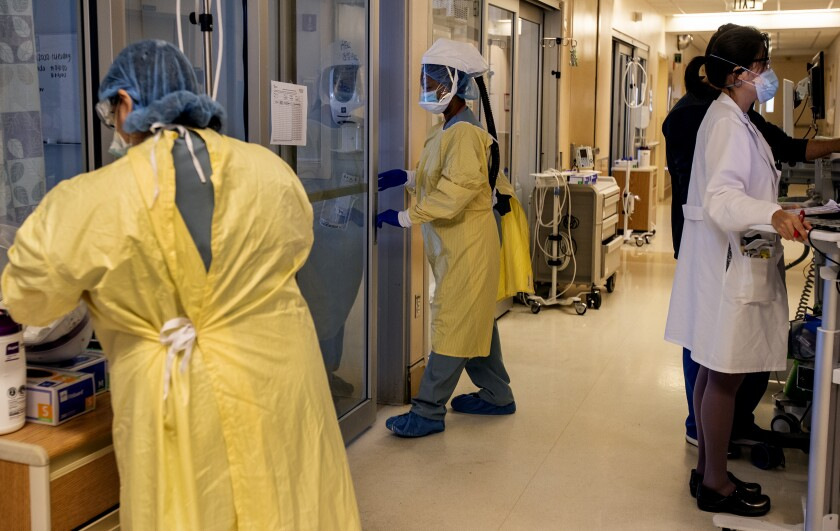 An ICU nurse wearing head-to-toe personal protective gear enters a room to treat a COVID-19 patient