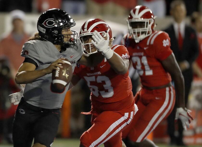 Santa Ana Mater Dei defensive lineman Joshua Sagiao pressures Corona Centennial quarterback Ala Mikaele.