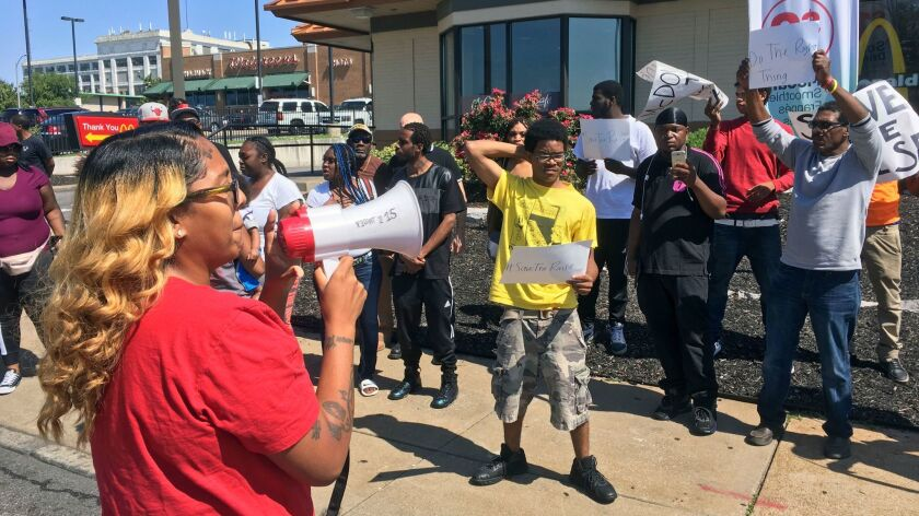 "Gennice Mackey leads a chant of ""Save the Raise!"" outside a McDonald's restaurant in St. Louis."