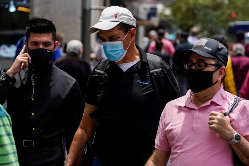 People wear masks in downtown Los Angeles on June 25.