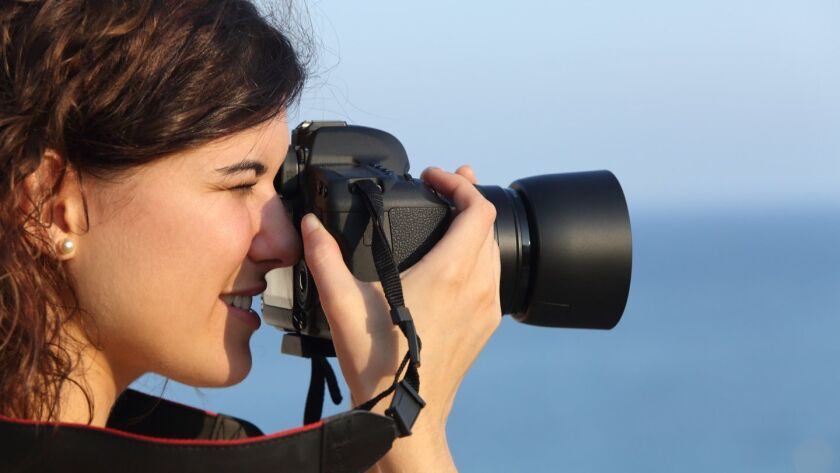 Attractive woman taking a photograph with her camera with the sea in the background