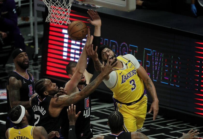 Lakers forward Anthony Davis tries a reverse lay-up, but runs in to the defense of the Clippers.