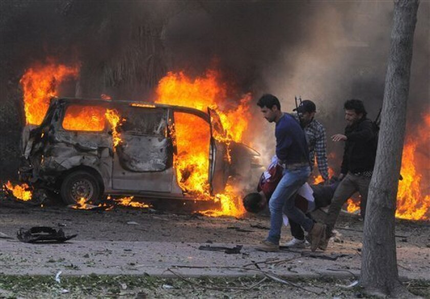 This photo released by the Syrian official news agency SANA, shows Syrian security agents carrying a body following a huge explosion that shook central Damascus, Syria, Thursday, Feb. 21, 2013. A car bomb shook central Damascus on Thursday, exploding near the headquarters of the ruling Baath party