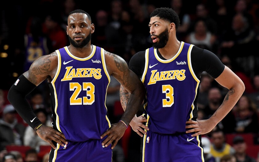 Lakers forwards LeBron James (23) and Anthony Davis (3) chat during a timeout while playing against the Trail Blazers in Portland on Dec. 6, 2019.