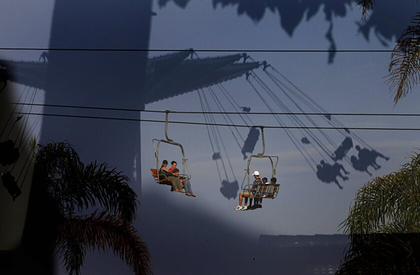 Visitors taking the Sky Ride overlook the midway from above while a Fun Zone ride is reflected in a window on the last day of the San Diego County Fair.