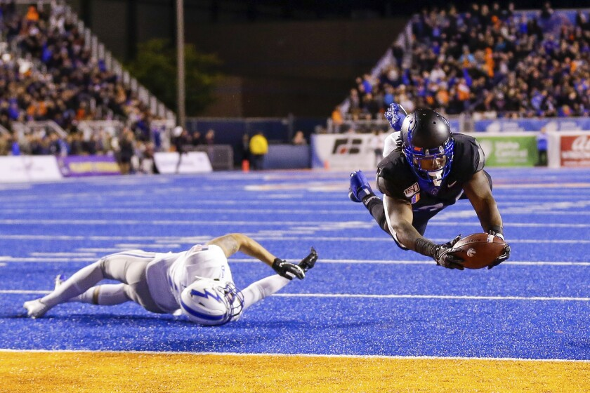 Boise State's Robert Mahone dives past Air Force's Jeremy Fejedelem on one of his two touchdown runs Sept. 20, 2019.