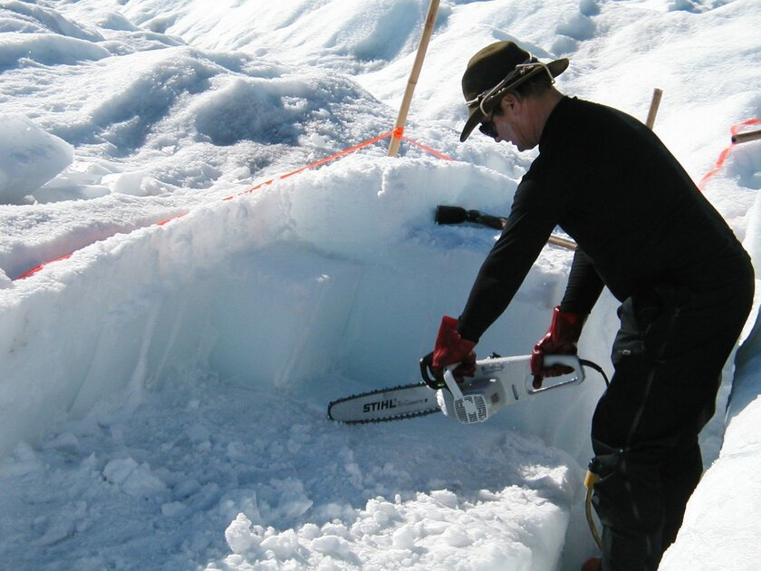Jeff Severinghaus, a professor of geosicences at Scripps Institution Oceanography, cuts 12,000 year-old ice with a chainsaw in Pakitsoq in western Greenland.