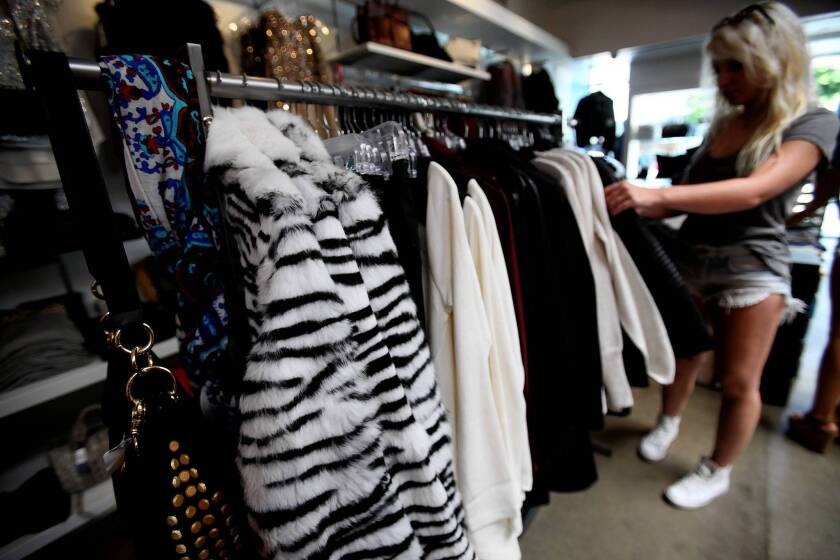 A shopper goes through the inventory at a Kitson in Los Angeles. Kitson plans to move banned items from the West Hollywood store to those outside the city limits.