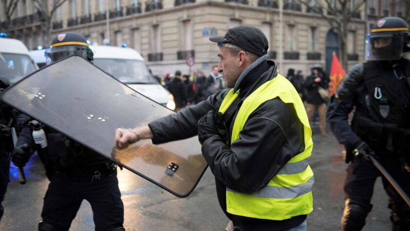 """A man punches the shield of a riot police officer on Jan. 19, 2019, in Paris, during a demonstration called by the """"yellow vest"""" movement as part of a nationwide protest against the high cost of living and government tax reforms."""