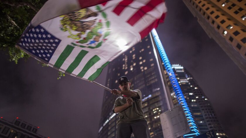 A protester waves a flag composed of elements of the U.S. and Mexican flags in front of the InterContinental in downtown Los Angeles, where President Trump stayed the night of March 13.