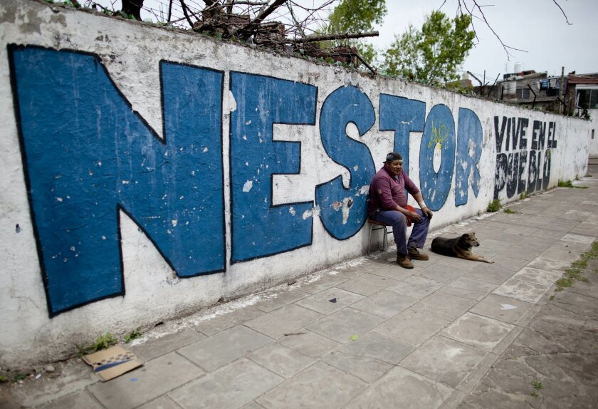 "In this Nov. 2, 2015 photo, Marcelo Monzon leans against a wall that reads in Spanish: ""Nestor lives among the people,"" referring to late president Nestor Kirchner, in Buenos Aires, Argentina. Monzon voted for Sergio Massa presidential candidate in the last general election and says he does not kno"