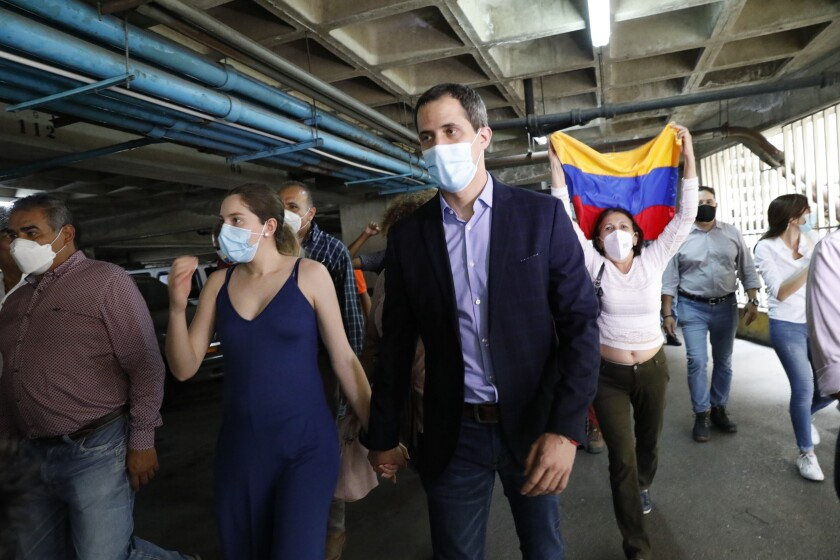 Opposition leader Juan Guaido and his wife Fabiana Rosales walk in the parking lot of their residential building after holding an impromptu press conference in Caracas, Venezuela, Monday, July 12, 2021. Guaido said security forces threatened his driver as he arrived home Monday. (AP Photo/Ariana Cubillos)