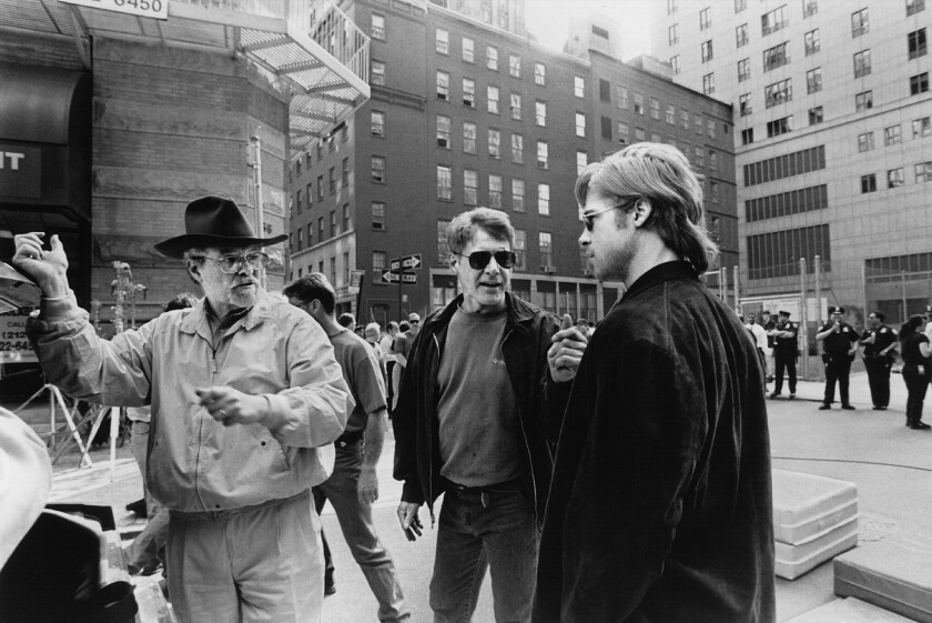 "Black-and-white image of Alan Pakula, left, Harrison Ford and Brad Pitt on the set of ""The Devil's Own"" in 1997."