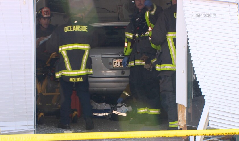 Firefighters move an injured woman Tuesday evening after a car crashed into the clubhouse at Villa Trieste, a 55+ senior-living community in Oceanside.