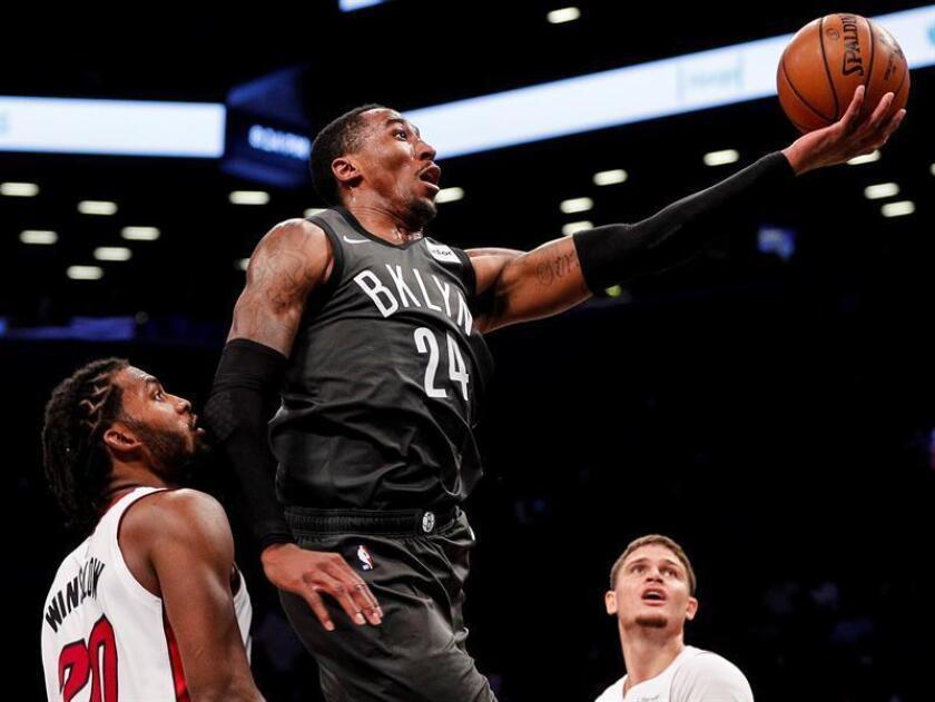 El delantero de los Brooklyn Nets Rondae Hollis-Jefferson (c) pasa frente a Justise Winslow (i) y James Johnson (d) de Miami Heat hoy, miércoles 14 de noviembre de 2018, en un juego de la NBA entre Miami Heat y Brooklyn Nets en Barclays Center en Brooklyn en Nueva York (EE.UU.). EFE