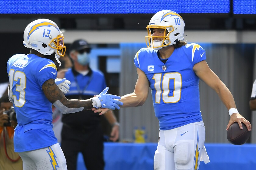 Justin Herbert (10) of the Los Angeles Chargers celebrates with Keenan Allen after running for a touchdown.