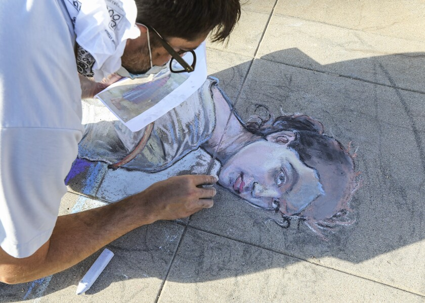 OB resident Erick Toussaint works on a one of his chalk art creations
