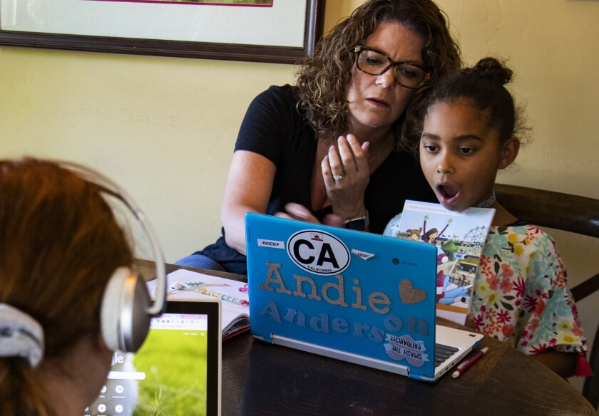 Kristen Bristow helps her daughter with a book report during a home-schooling session in Riverside.