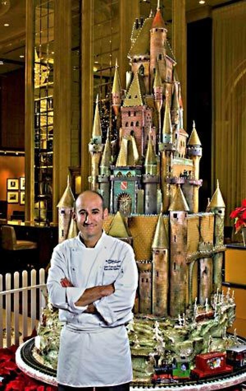 Executive pastry chef Jean-Francois Houdre proudly stands by his Sugar Castle, part of the annual holiday display at the hotel.