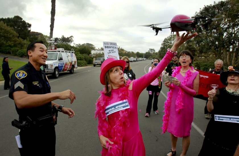 San Diego Police Sgt. Dan Sayasane looks on as a small radio controlled quadcopter to simulate a drone lands in the hand of CodePink co-founder Medea Benjamin during an anti-drone protest in front of the La Jolla home of James Neal Blue, CEO of General Atomics, makers of drones used by the military