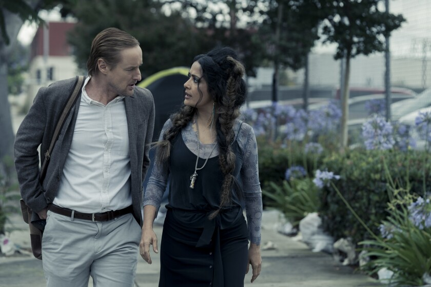 "Owen Wilson and Salma Hayek walk in the rain in ""Bliss."""