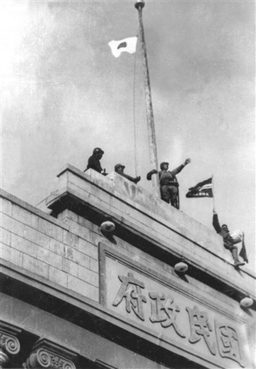 """FILE - In this Dec. 1937 file photo Japanese soldiers cheer as they hoist their flag from the roof of the central government building after they seized Nanking in the Second Sino Japanese War. Japan acknowledged its wartime military caused tremendous damage to China in the """"Rape of Nanking"""" massacre, but the two sides failed again to agree on the death toll in a report published this week. The massacre was one of the worst incidents in Japan's invasion of China during the first half of the 20th century. (AP Photo)"""