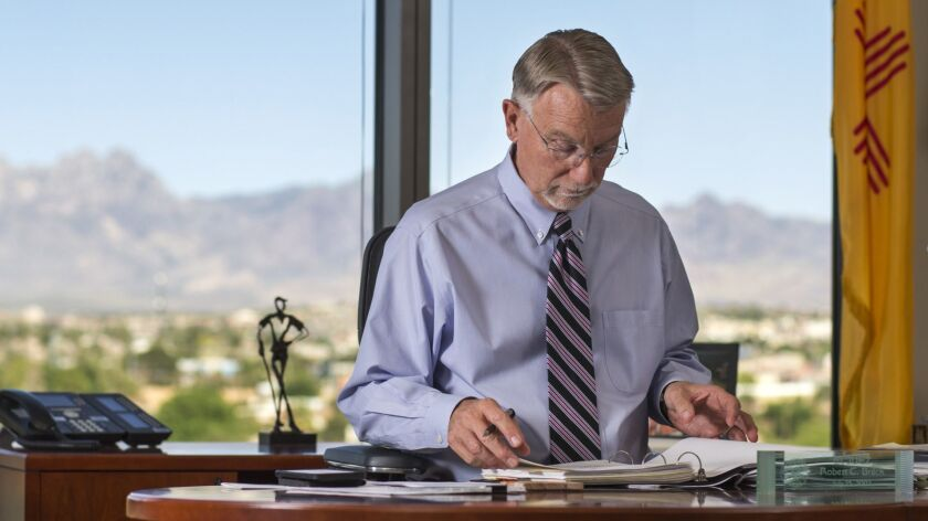 Backdropped by the Organ Mountains, federal judge Robert Brack reviews his docket in his chambers a