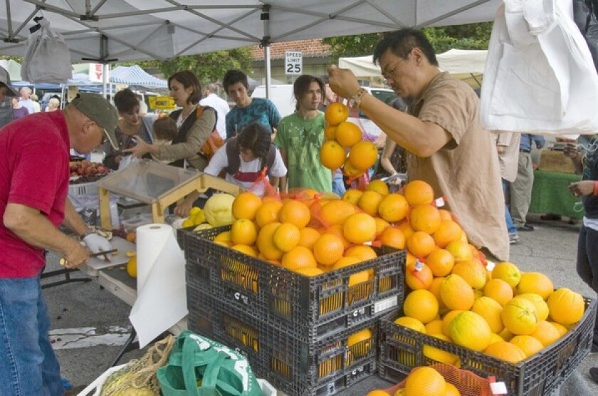 A customer at the Etheridge Farms stand at the South Pasadena farmers market picks out navel oranges grown in Dinuba. RELATED: Farmers market flap in South Pasadena as new manager shakes things up