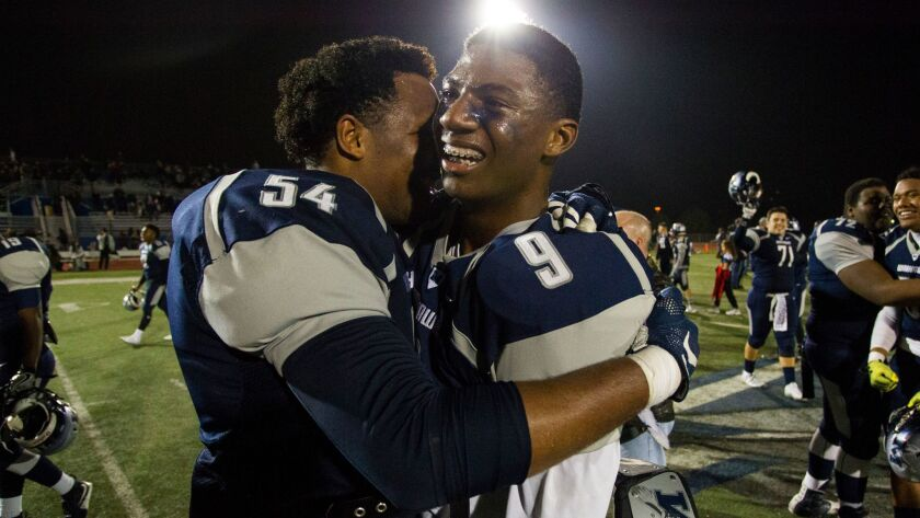 Madison teammates Donte Grady (54) and Terrell Carter (9) embrace after the Warhawks' second amazing victory in as many weeks.