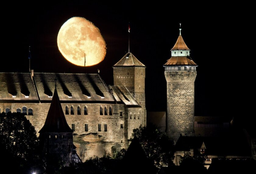 The moon is seen rising behind the Imperial Castle in Nuremberg, Germany, in October. A new study offers an explanation for the moon's mysterious tilt.