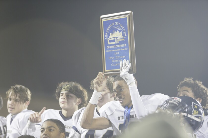 Mason White (19) lifts the winning plaque as Birmingham celebrates after the 2019 City Section Open Division title game.
